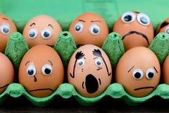 Έννοια διασκέδασης: ακατέργαστα αυγά με googly τα μάτια και συρμένα χαρακτηριστικά γνωρίσματα στον κλονισμό και λυπημένος ενώ κάθ Στοκ εικόνα με δικαίωμα ελεύθερης χρήσης