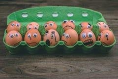 Έννοια διασκέδασης: ακατέργαστα αυγά με googly τα μάτια και συρμένα χαρακτηριστικά γνωρίσματα στον κλονισμό και λυπημένος ενώ κάθ Στοκ εικόνες με δικαίωμα ελεύθερης χρήσης