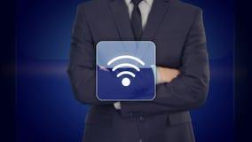 Έννοια Διαδικτύου - επιχειρηματίας που πιέζει το κουμπί WI-Fi στις εικονικές οθόνες ελεύθερη απεικόνιση δικαιώματος