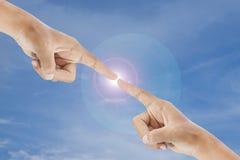 Έννοια δύο αφή χεριών με την επίδραση φλογών στο υπόβαθρο μπλε ουρανού Στοκ Εικόνες