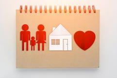 Έννοια εγχώριων γλυκιά σπιτιών το έγγραφο οικογενειών και σπιτιών που κόβεται με με το κόκκινο Στοκ Φωτογραφίες