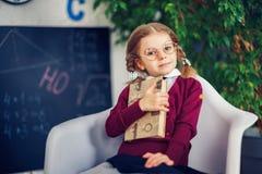 Έννοια εκμάθησης με το χαριτωμένο μικρό κορίτσι που κρατά ένα βιβλίο στοκ εικόνες
