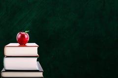 Έννοια εκπαίδευσης με τη Apple στα βιβλία και το υπόβαθρο πινάκων κιμωλίας Στοκ φωτογραφίες με δικαίωμα ελεύθερης χρήσης