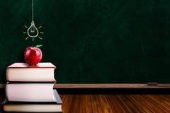 Έννοια εκπαίδευσης με τη Apple στα βιβλία και Lightbulb σε Blackboar Στοκ φωτογραφία με δικαίωμα ελεύθερης χρήσης