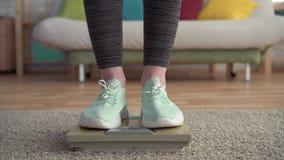 Έννοια ελέγχου βάρους, πόδια των γυναικών στις κλίμακες πατωμάτων φιλμ μικρού μήκους