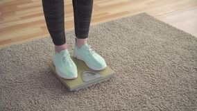 Έννοια ελέγχου βάρους, πόδια των γυναικών στις κλίμακες πατωμάτων στο καθιστικό απόθεμα βίντεο