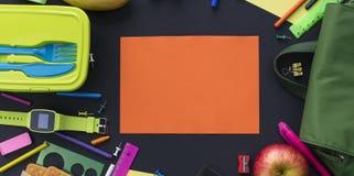 Έννοια εμβλημάτων πίσω στα χαρτικά σακιδίων πλάτης σχολικών μήλων στο μαύρο υπόβαθρο Στοκ Φωτογραφίες