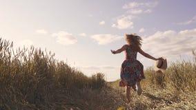 Έννοια ενός ξένοιαστου και ευτυχούς καλοκαιριού Ένα κορίτσι τρέχει κατά μήκος ενός τομέα σίτου που κρατά ένα καπέλο αχύρου υποστη φιλμ μικρού μήκους