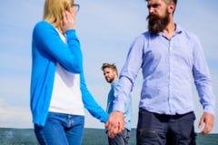 Έννοια εξαπάτησης Το άτομο βρήκε ή ανίχνευσε τη φίλη που εξαπατά τον που περπατά με ένα άλλο άτομο Πλήρη ζηλότυπα βλέμματα φίλων Στοκ Φωτογραφίες