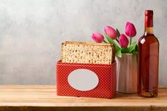 Έννοια εορτασμού Passover με το μπουκάλι κρασιού, matzoh και τα λουλούδια τουλιπών Στοκ Εικόνες