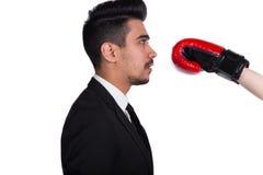 Έννοια επιχειρησιακής σύγκρουσης Ο νεαρός άνδρας στο κοστούμι παίρνει το χτύπημα από τον μπόξερ στα εγκιβωτίζοντας γάντια Στοκ φωτογραφία με δικαίωμα ελεύθερης χρήσης