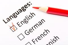 Έννοια ερωτηματολογίων Γλώσσες με τα αγγλικά, γερμανικά, γαλλικά, ισπανικά τετραγωνίδια με το κόκκινο μολύβι Κλείστε επάνω την ει στοκ εικόνες