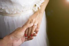 Έννοια ζευγών γαμήλιας αγάπης: τεθειμένα νεόνυμφος γαμήλια δαχτυλίδια στη νύφη Στοκ Φωτογραφία