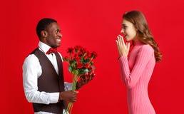 Έννοια ημέρας βαλεντίνων ` s ευτυχές νέο ζεύγος με την καρδιά, λουλούδια, δώρο στο κόκκινο στοκ εικόνες