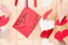Έννοια ημέρας βαλεντίνων ` s κόκκινη ένωση φακέλων εγγράφου origami σε έναν συνδετήρα στο ξύλινο υπόβαθρο με τις καρδιές εγγράφου Στοκ Εικόνες