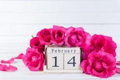Έννοια ημέρας και αγάπης βαλεντίνων Ρόδινα τριαντάφυλλα με το κείμενο στις 14 Φεβρουαρίου στο ξύλινο ημερολόγιο φραγμών στο άσπρο στοκ εικόνες