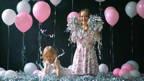 Έννοια ημέρας μητέρων Η ευτυχή γυναίκα και το νέο κορίτσι γιορτάζουν το plaing κομφετί γενεθλίων απόθεμα βίντεο