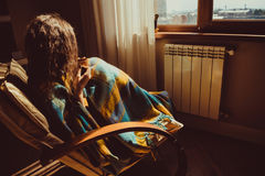 Έννοια διακοπών χειμώνα και Χριστουγέννων Νέα συνεδρίαση γυναικών στην άνετη σύγχρονη καρέκλα κοντά στο θερμαντικό σώμα με την κο Στοκ Εικόνες