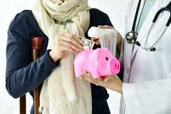 Έννοια ιατρικής και ασφάλειας υγείας, γιατρός που κρατά τη piggy τράπεζα και τα χρήματα στο υπόβαθρο νοσοκομείων στοκ εικόνα με δικαίωμα ελεύθερης χρήσης
