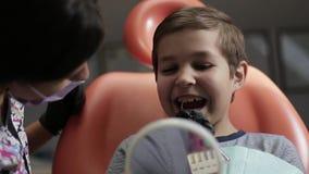 Έννοια ιατρικής, οδοντιατρικής και υγειονομικής περίθαλψης - θηλυκός οδοντίατρος με τον ασθενή παιδιών στην οδοντική καρέκλα ρύθμ απόθεμα βίντεο