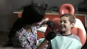 Έννοια ιατρικής, οδοντιατρικής και υγειονομικής περίθαλψης - θηλυκός οδοντίατρος με τον ασθενή παιδιών στην οδοντική καρέκλα ρύθμ φιλμ μικρού μήκους