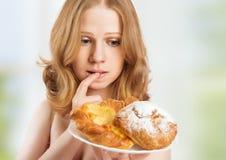 Έννοια διατροφής. γυναίκα σε μια διατροφή που ονειρεύεται τα κουλούρια Στοκ Εικόνα