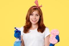 Έννοια καθαρισμού και οικιακών Σκληρά απασχομένος στην αρκετά χαμογελώντας νέα θηλυκή νοικοκυρά στα προστατευτικά γάντια κρατήστε στοκ εικόνα