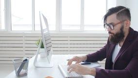 Έννοια και εργασίας του γραφείου Νέος μοντέρνος υπάλληλος που εξετάζει το όργανο ελέγχου υπολογιστών κατά τη διάρκεια της εργάσιμ απόθεμα βίντεο