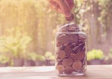 Έννοια και χέρι χρημάτων αποταμίευσης που βάζουν τα χρήματα στην ανάπτυξη μπουκαλιών Στοκ φωτογραφία με δικαίωμα ελεύθερης χρήσης