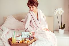 Έννοια καλημέρας Η γυναίκα στη συνεδρίαση μπουρνουζιών στο κρεβάτι και έχει το δίσκο προγευμάτων της με τον καφέ, macaroons, χυμό στοκ εικόνες