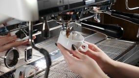 Έννοια καφετεριών Κλείστε επάνω των θηλυκών χεριών barista κρατώντας ένα φλυτζάνι στον καφέ κατασκευάζοντας τη μηχανή Διαδικασία  φιλμ μικρού μήκους