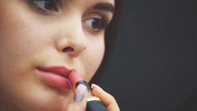 Έννοια, κεφάλι και ώμοι ομορφιάς της νέας γυναίκας που εξετάζει τα χείλια καμερών και ζωγραφικής με το ροδαλό κραγιόν closeup απόθεμα βίντεο
