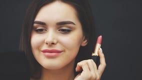 Έννοια, κεφάλι και ώμοι ομορφιάς της νέας γυναίκας που εξετάζει τα χείλια καμερών και ζωγραφικής με το ροδαλό κραγιόν closeup φιλμ μικρού μήκους