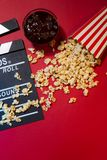 Έννοια κινηματογράφων Clapperboard, εισιτήριο και popcorn στο κόκκινο backgrou Στοκ Φωτογραφία