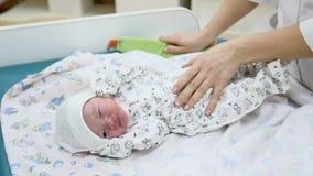 Έννοια κλινικών μητρότητας το νήπιο είναι στον πίνακα που παίρνει έτοιμο για τις ιατρικές διαδικασίες Swaddling μωρό γιατρών Νεογ φιλμ μικρού μήκους