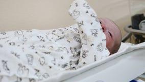 Έννοια κλινικών μητρότητας Το Unrecognizable νήπιο είναι στον πίνακα που παίρνει έτοιμο για τις ιατρικές διαδικασίες Νεογέννητος  φιλμ μικρού μήκους