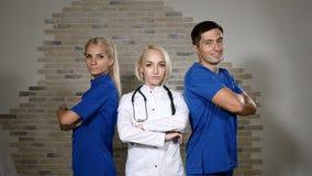 Έννοια κλινικών υγείας Τοποθέτηση γιατρών Η ομάδα τριών νέων επιτυχών ιατρικών εργαζομένων στα άσπρα και μπλε unuforms στέκεται απόθεμα βίντεο