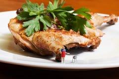 Έννοια κομμάτων σχαρών Μικροσκοπικός μάγειρας αριθμού ενάντια στο μεγάλο ψημένο στη σχάρα bbq κοτόπουλο σε ένα άσπρο πιάτο Στοκ φωτογραφία με δικαίωμα ελεύθερης χρήσης