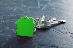 Έννοια κτημάτων με το βασικό, πράσινο keychain με το σύμβολο σπιτιών, ecotechnologies Στοκ εικόνες με δικαίωμα ελεύθερης χρήσης