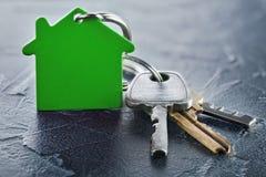 Έννοια κτημάτων με το βασικό, πράσινο keychain με το σύμβολο σπιτιών, ecotechnologies Στοκ εικόνα με δικαίωμα ελεύθερης χρήσης
