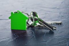 Έννοια κτημάτων με το βασικό, πράσινο keychain με το σύμβολο σπιτιών, ecotechnologies Στοκ Φωτογραφία