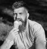 Έννοια λιχουδιών Γενειοφόρο άτομο με τον κώνο παγωτού Το άτομο με τη γενειάδα και mustache στο ευτυχές πρόσωπο γλείφει το παγωτό, Στοκ φωτογραφία με δικαίωμα ελεύθερης χρήσης