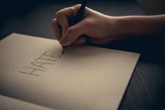 Έννοια μίσους - μίσος γραψίματος χεριών στο βιβλίο στοκ εικόνα με δικαίωμα ελεύθερης χρήσης