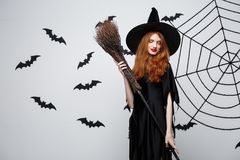 Έννοια μαγισσών αποκριών - πορτρέτο της όμορφης νέας μάγισσας με το σκουπόξυλο πέρα από τον γκρίζο τοίχο με τον Ιστό ροπάλων και  Στοκ Εικόνες