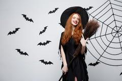 Έννοια μαγισσών αποκριών - πορτρέτο της όμορφης νέας μάγισσας με το σκουπόξυλο πέρα από τον γκρίζο τοίχο με τον Ιστό ροπάλων και  Στοκ Φωτογραφία
