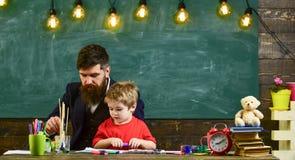 Έννοια μαθήματος σχεδίων Παιδί και δάσκαλος στα πολυάσχολα πρόσωπα που χρωματίζουν, σχεδιασμός Δάσκαλος με τη γενειάδα, πατέρας κ στοκ εικόνες με δικαίωμα ελεύθερης χρήσης