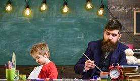 Έννοια μαθήματος τεχνών Παιδί και δάσκαλος στα πολυάσχολα πρόσωπα που χρωματίζουν, σχεδιασμός Δάσκαλος με τη γενειάδα, πατέρας κα στοκ εικόνα
