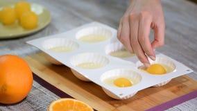 Έννοια με τα ανθρώπινα ίχνη Κατασκευή του σύγχρονου mousse κέικ με την πορτοκαλιά πλήρωση απόθεμα βίντεο