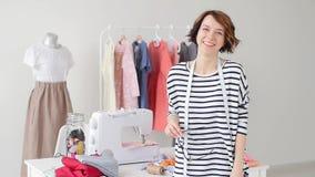 Έννοια μικρών επιχειρήσεων και χόμπι Νέο seamstress χαμογελά στα πλαίσια των προϊόντων τους στο στούντιό του φιλμ μικρού μήκους