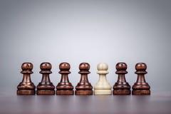 Έννοια μοναδικότητας σκακιού πέρα από το γκρίζο υπόβαθρο Στοκ Φωτογραφίες